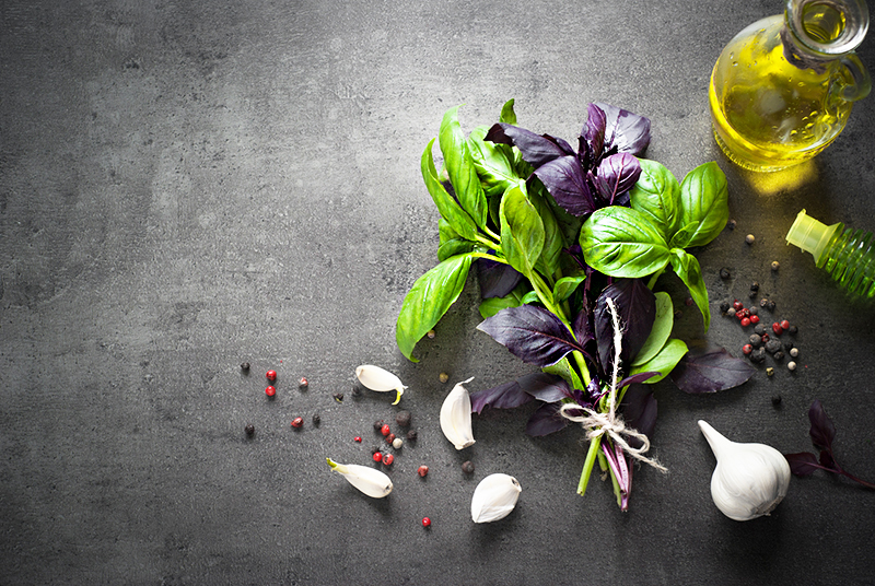 Basil leaves, garlic, pepper and olive oil at dark slate background. Space for text. Ingredients for cooking.